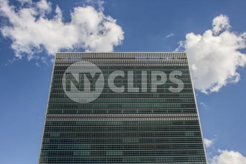 UN Building - close-up on top of United Nations from front - isolated on blue sky with clouds on beautiful sunny summer day