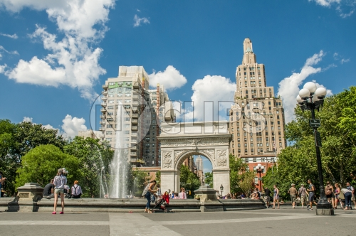 Washington Square Park in summer with fountain spraying water and famous arch, people enjoying beautiful weather