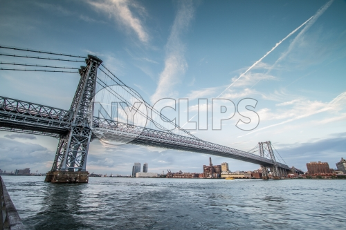 Williamsburg Bridge in Brooklyn in late afternoon during day with East River water and blue sky