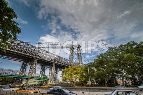 Williamsburg Bridge with Houston Street exit sign in Manhattan with cars driving on FDR Drive highway on bright sunny day