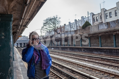 woman on cell phone - outdoor subway platform in winter - elevated train station tracks