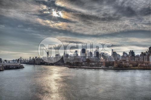 Manhattan skyline from across East River in late afternoon early evening - sun beaming through clouds onto water in HDR