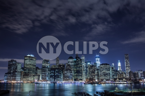 Manhattan skyline with incomplete Freedom Tower at night - clouds overhead across East River water in HDR