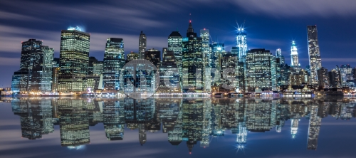 Manhattan skyline with unfinished Freedom Tower under construction at night across East River in HDR