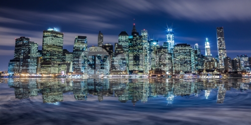 Manhattan skyline glowing with Freedom Tower under construction late at night across East River in HDR