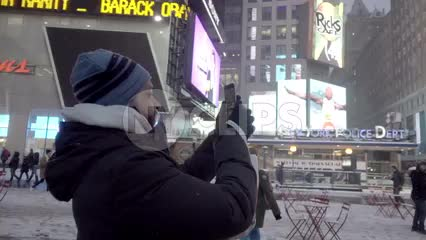 Middle-Eastern man taking video and pictures with smartphone in Times Square - snowing in winter at night