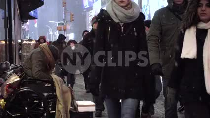 sad homeless man disabled in wheelchair on cold night - snowing in Times Square with tourists walking by ignoring tragedy