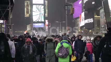 people crossing street - busy crowded Times Square crosswalk - snowing in Manhattan winter