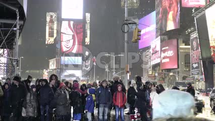 people at crosswalk waiting on busy Times Square intersection - snowing at night in slow motion