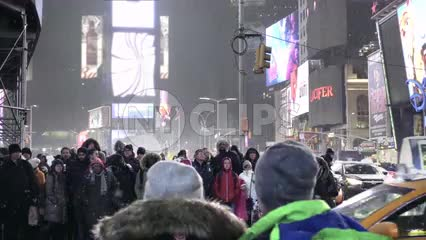 people waiting for taxis to cross - taxicabs driving across crosswalk in Times Square at night - snowing in Manhattan