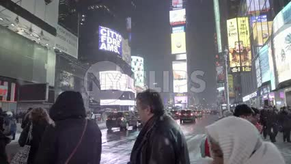 busy winter night in Times Square, snowing on traffic officer and tourists - NYC