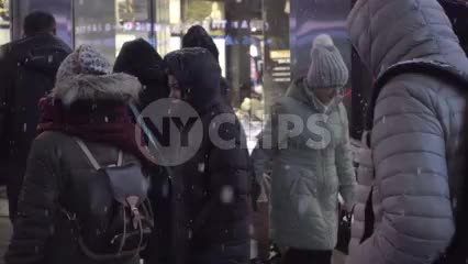 homeless man on street in blankets and rags with sign - wheelchair snowing at night in Times Square - slow motion NYC