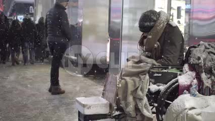 snowflakes falling and people passing by homeless man in wheelchair on street - snowing at night in winter