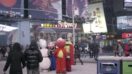 people walking in the snow in Times Square - cartoon characters costumes and subway station lights - snowing at night in New York City
