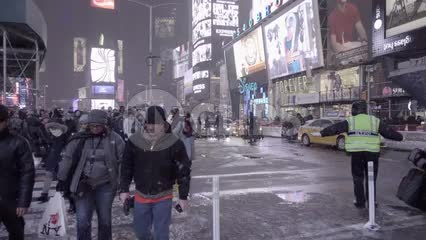people walking in snow at night in Times Square crosswalk, slow motion NYC