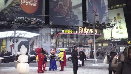 performers in Disney costumes - snowman in Times Square, snowing at night with bright lights on subway station sign - NYC