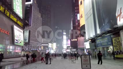 couple in Times Square night - snowing with tourists looking up and pointing at bright lights in New York City
