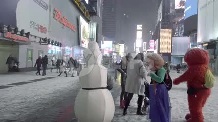 Elmo and Disney characters in costume taking photograph with tourist in Times Square winter blizzard - snowing at night