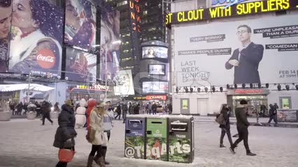 people walking past garbage and recycling bins in snow - snowing in Times Square at night