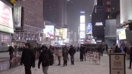 ads and red picnic tables in middle of Times Square, snowing in cold winter, people with coats and hats