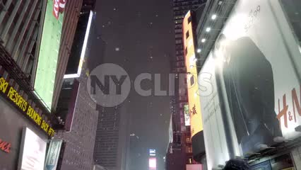 tilting down from night sky and bright billboards, ads in Times Square - snowing in slow motion