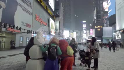 tourists with stroller taking pictures with Elmo and snowman at night in Times Square, snowing in winter in NYC