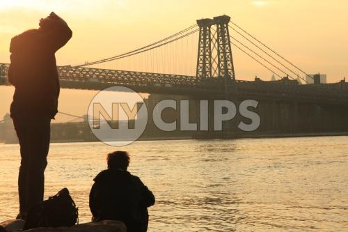 Manhattan Bridge at sunset - people enjoying view of beautiful orange sky over East River from Brooklyn