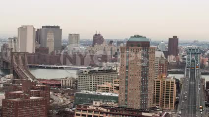 Manhattan and Brooklyn Bridge timelapse over East River with buildings on cloudy day - cars speeding in traffic