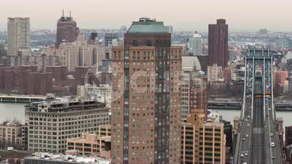 zooming out from Manhattan and Brooklyn Bridges - cars speeding across bridge in timelapse over East River with buildings on cloudy day