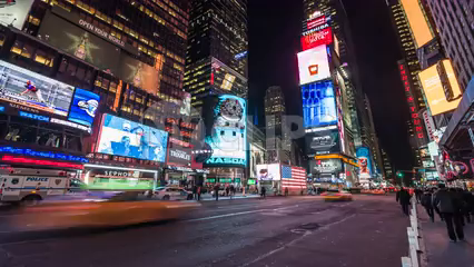 Times Square at night with bright lights, ads, billboards and traffic - 4K in NYC