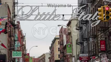 welcome to Little Italy sign in Chinatown on Chinese New Year parade - crowded with people behind police barrier - traffic cops