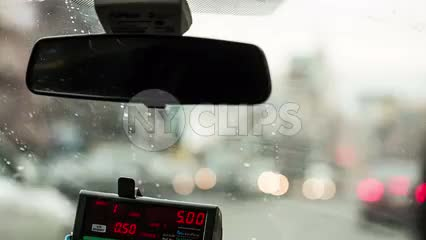 taxi cab driving on Houston Street with Empire State Building view in windshield - rearview mirror and meter in front seat