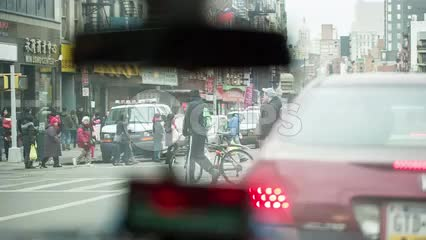 taxi cab stopped at busy intersection in Chinatown with people crossing street - meter and rearview mirror