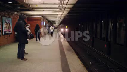 R train entering subway station in slow motion - people on platform