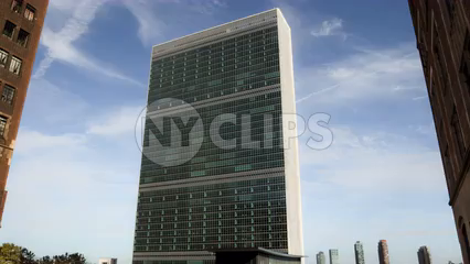 full shot of UN building in Midtown Manhattan flanked between two buildings - 4K timelapse during the day with blue sky