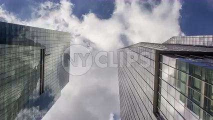 upward angle of two skyscrapers in Midtown Manhattan during the day - 4k timelapse of blue sky with clouds floating overhead