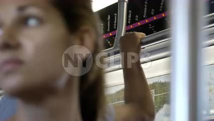 close-up on beautiful woman's face, riding 7 Train - standing on crowded subway with passengers