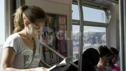 beautiful sporty woman reading on elevated subway train, standing in summer