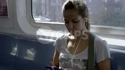 gorgeous girl on elevated train riding with earbuds on sunny summer day shining through window