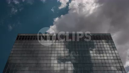 top of skyscraper - looks like UN building with blue sky and clouds - 4K timelapse in Manhattan