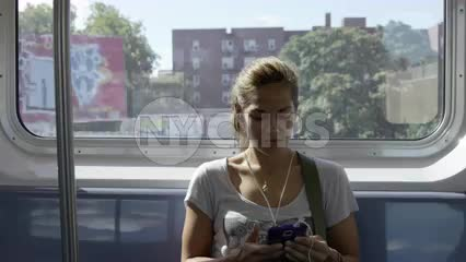 gritty neighborhood in Queens with graffiti on buildings passing in window background - woman listening to music on headphones