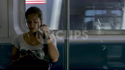 beautiful woman listening to music on subway - elevated train with graffiti buildings in Queens passing in background