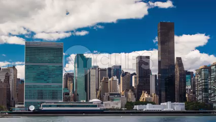UN Building in skyline daytime with blue sky and clouds - 4K HDR timelapse of Manhattan