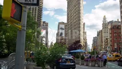 Flatiron Building on 5th Ave and Broadway with cars and taxicab driving in summer