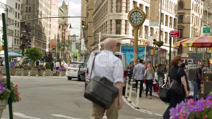 people walking on 5th Ave with famous clock on summer day in Manhattan