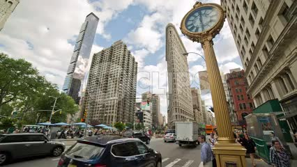 famous 5th Ave clock with Flatiron Building skyscraper in Manhattan - summer day