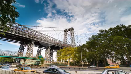 Williamsburg Bridge with cars driving during the day - 4K timelapse with blue sky and clouds in NYC