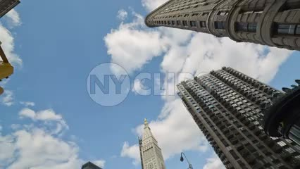 rotating shot of Flatiron Building and other skyscrapers on 5th Ave in Manhattan - street view upward blue sky on summer day