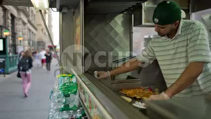 Middle-Eastern man preparing - cooking kabobs in Halal food truck outside on summer day