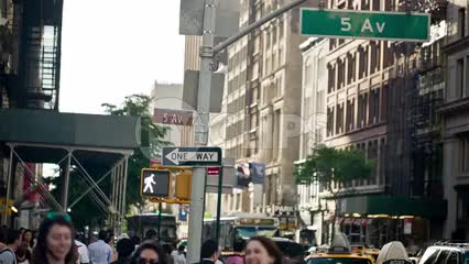 5th Avenue sign at busy intersection on 14th st in summer - people crossing street